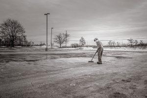 Ein Mann kehrt einen Parkplatz